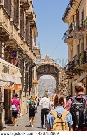 Rear View Of Tourists Walking Along Ancient Streets Of Taormina On Hot Summer Day: Taormina, Italy -