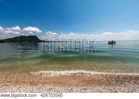 Beautiful Beach On Lake Garda (lago Di Garda) In Front Of The Small Town Of Garda. Headland Of San V