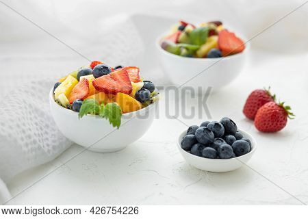 Fresh Fruit Salad With Fresh Strawberries, Kiwi, Apricots And Blueberries, Decorated With Leaves Of