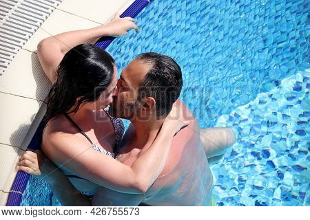 Marmaris, Turkey - July 2021: Passionate Couple Hugs And Kisses In The Swimming Pool Of Tourist Reso