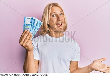 Caucasian young man with long hair holding 1000 hungarian forint banknotes celebrating achievement with happy smile and winner expression with raised hand