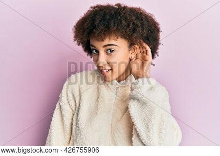 Young hispanic girl wearing casual clothes smiling with hand over ear listening and hearing to rumor or gossip. deafness concept.