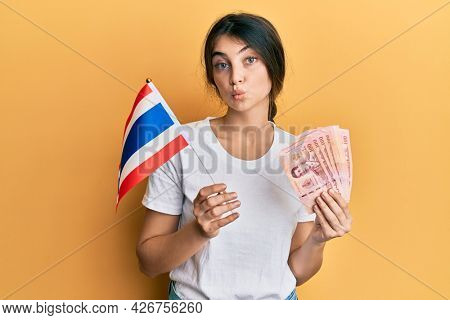 Young caucasian woman holding thailand flag and baht banknotes looking at the camera blowing a kiss being lovely and sexy. love expression.