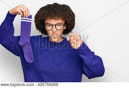 Young hispanic girl holding sporty sock annoyed and frustrated shouting with anger, yelling crazy with anger and hand raised