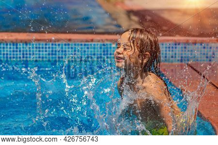 Happy Little Boy Having Fun in the Pool. Playing with Water. Enjoying Warm Sunny Day in Aquapark. Summer Holidays Concept.