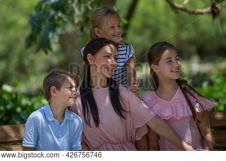 Portrait of a Happy Big Family Outdoors. Looking a Side. Beautiful Young Mother Spending Time with Her Three Precious Kids on Enjoying Fresh Air.