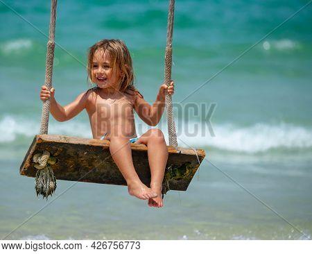 Baby Boy Enjoying Swing on the Beach. Happy Child on Summer Holidays.