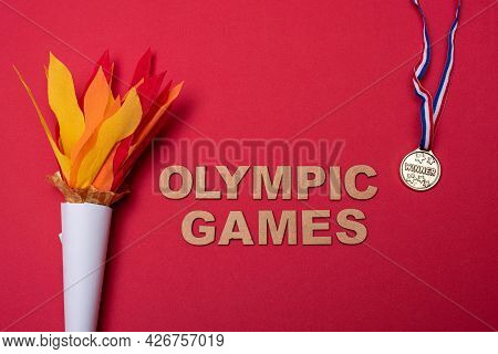 Xalapa, Veracruz, Mexico- July 8, 2021: Paper Torch And Medal On Red Background.