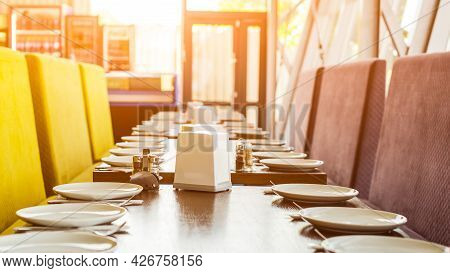 Tables Set For Meal In Modern Cafeteria. A Lot Of White Ceramic Plates On A Banquet Table. Served Ta
