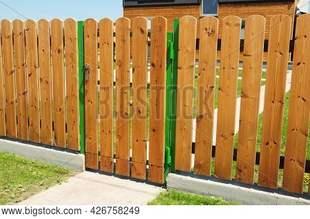 A Traditional, Neat Wood Picket Fencing With A Door, Gate. Wood Picket Fencing Around The House, Cot