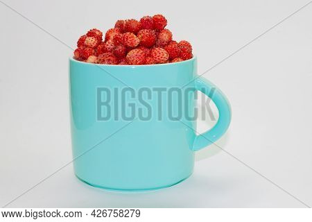 Full Turquoise Ceramic Cup Of Ripe Wild Strawberry Isolated On Light Background.