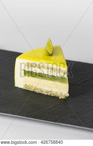 Close-up Piece Of Mousse Cake Covered Yellow Mirror Glaze With A Slice Of Lime. French Dessert