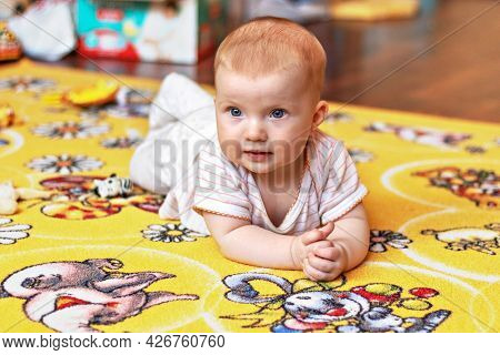 A Small Child On A Rug Among Toys.