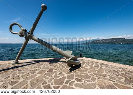 Large Anchor In Front Of The Port Of Bardolino Village, Tourist Resort On The Coast Of Lake Garda (l