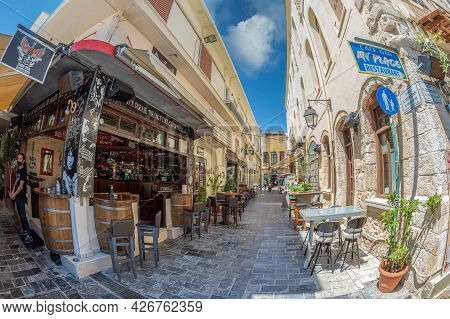 Rethymno, Crete Island, Greece - June 18, 2021: View With Small And Picturesque Street Terraces Loca
