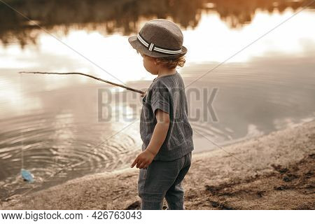 Side View Of Cute Toddler Boy In Summer Clothes And Hat Standing On Lake Shore With Toy Fishing Rod