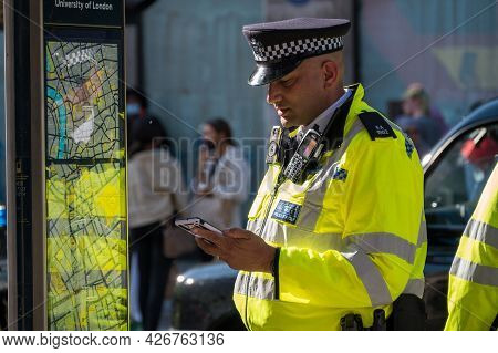 London - May 29, 2021: British Police Officer In A High Visibility Jacket Looks At A Mobile Cell Pho