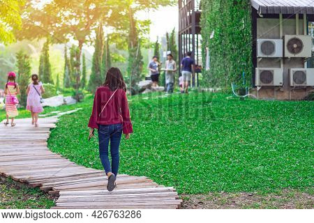 Back View Of Asian Woman Walk Alone On Pathway Through Green Garden. Female Relaxing Alone In The Pa