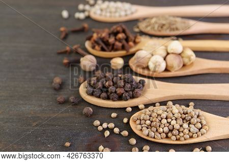 Assortment Of Spices In Spoons On Wooden Background
