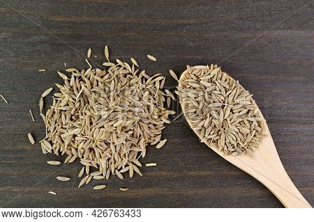 Heap Of Dried Cumin Seeds On Wooden Background And In A Wooden Spoon