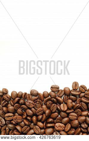Dark Brown Roasted Coffee Beans Isolated On White Background With Copy Space