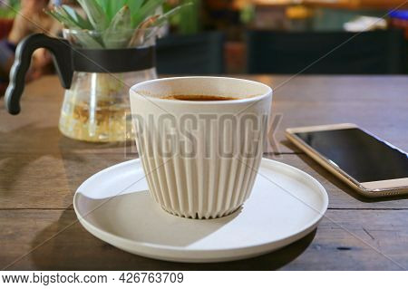 Cup Of Hot Coffee On A Wooden Table With Blank Screen Smartphone In Background