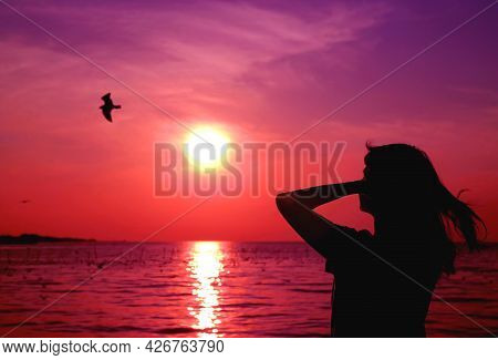 Pop Art Style Of A Silhouette Of Woman Looking Up To Vivid Purple Pink Colored Sunrise Sky With A Fl