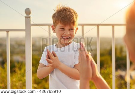 Happy Little Ginger Boy And Recognizable Mom Having Fun And Clapping Hands While Spending Sunny Summ