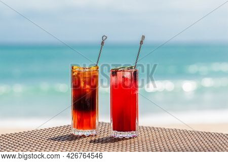Beautiful Refreshing Fruit Cocktails On Table On Beach, Blue Sea On Background. Orange And Strawberr