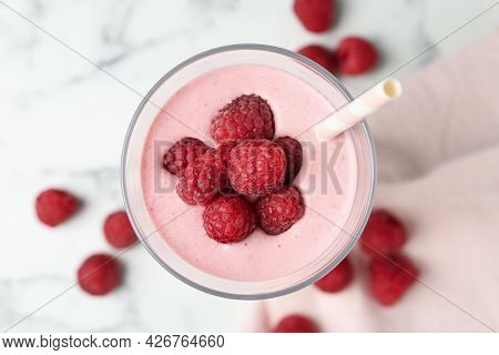 Yummy Raspberry Smoothie In Glass On White Marble Table, Top View