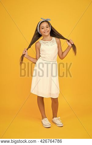 Beautify Your Hairstyle. Happy Girl Wear Long Hairstyle Yellow Background. Little Child Hold Brunett