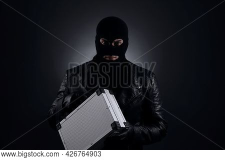 Man Wearing Knitted Balaclava With Metal Briefcase On Black Background