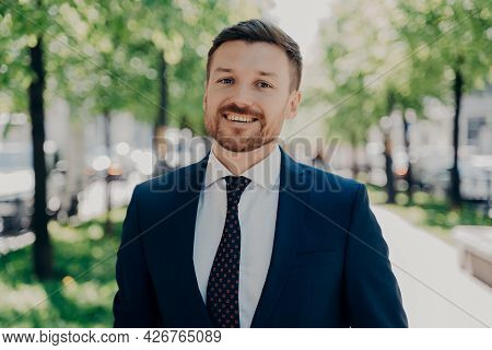 Close Portrait Of Smiling Handsome Young Bearded Man In Dark Blue Suit Walking Outside In Sunny Day