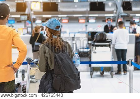 Back View Of Airline Passenger Wear Face Mask To Prevent Corona Virus (covid-19) Wait To Check In Co