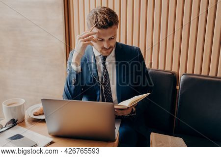 Successful Financier In Elegant Suit With Thoughtful Look In Earbuds And With Laptop Working Online