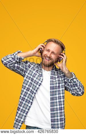 Cheerful Bearded Guy In Checkered Shirt Smiling And Adjusting Headphones While Listening To Favorite