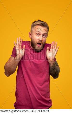 Astonished Bearded Blond Man In Red T Shirt Raising Hands And Looking At Camera With Opened Mouth Ag