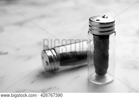 Biodegradable Dental Flosses In Glass Jars On White Marble Table, Closeup. Space For Text
