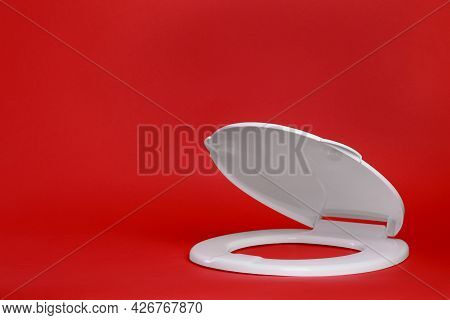 New White Plastic Toilet Seat On Red Background, Space For Text