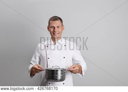 Happy Male Chef With Cooking Pot On Light Grey Background