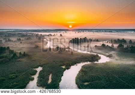 Aerial Elevated View Green Meadow And River Landscape In Misty Foggy Morning. Top View Of Beautiful