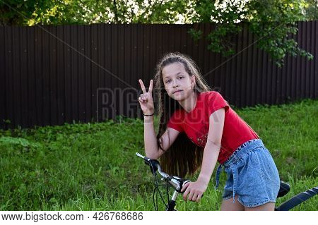 Beautiful Teenage Girl In Denim Shorts And T-shirt Is Learning To Ride Bicycle Through Streets Of Su