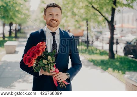 Smiling Stylish Stubbly Gentleman In Dark Blue Tuxedo With Big Bouquet Of Red Roses Walking Along Gr
