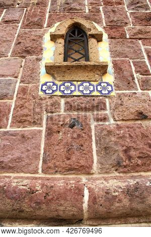 Selective Focus Of Old Rustic Medieval, Stone Wall With Small Window And Ironwork
