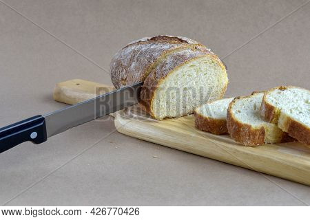 Sliced Fresh Bread Loaf And Knife On Cutting Board. Baked Bread Lies On Table On Craft Paper, Home B