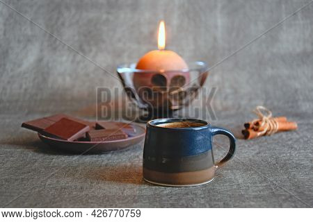 Cup Of Coffee, Dark Chocolate, Cinnamon Sticks And Burning Decorative Candle, Close-up, Selective Fo