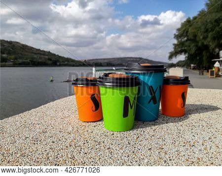 Four Multi-colored Disposable Portable Paper Coffee Cups Of Different Sizes On Background Of River.