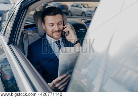 Good Looking Happy Executive Manager In Stylish Formal Wear Reads Newspaper On Backseat Of Car In Sa