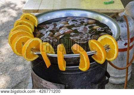 Mulled Wine Street Trading. A Large Bowl With A Drink, Decorated With Slices Of Orange. Cooking On A