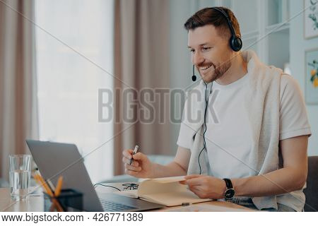 Glad Male Tutor Gives Online Lessons Comunicates Distantly With Trainee Uses Headphones With Microph